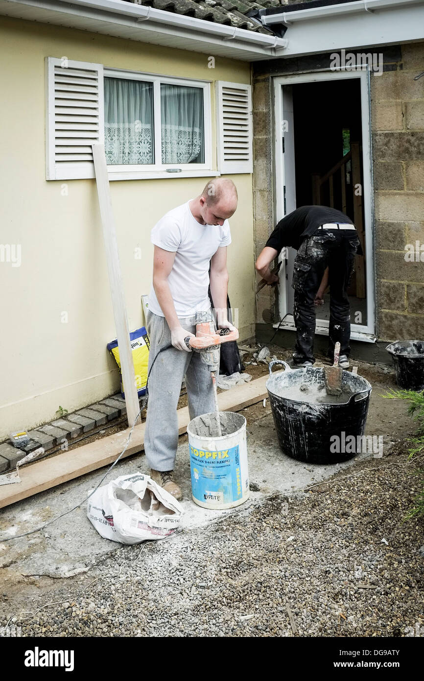 Plasterers working on a doorway to a house. Stock Photo