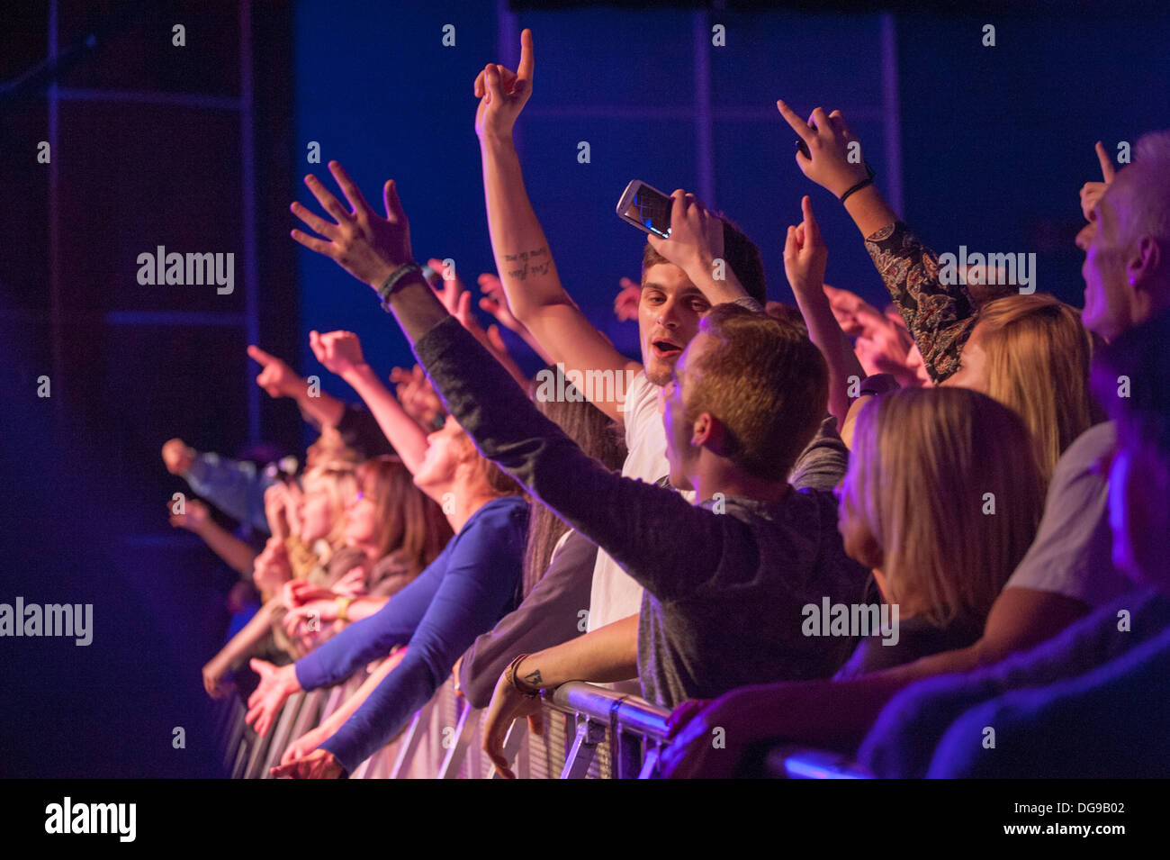 Music fans at a gig crushed against the barrier at the front cheering, clapping and screaming at a band on stage - Stock Image