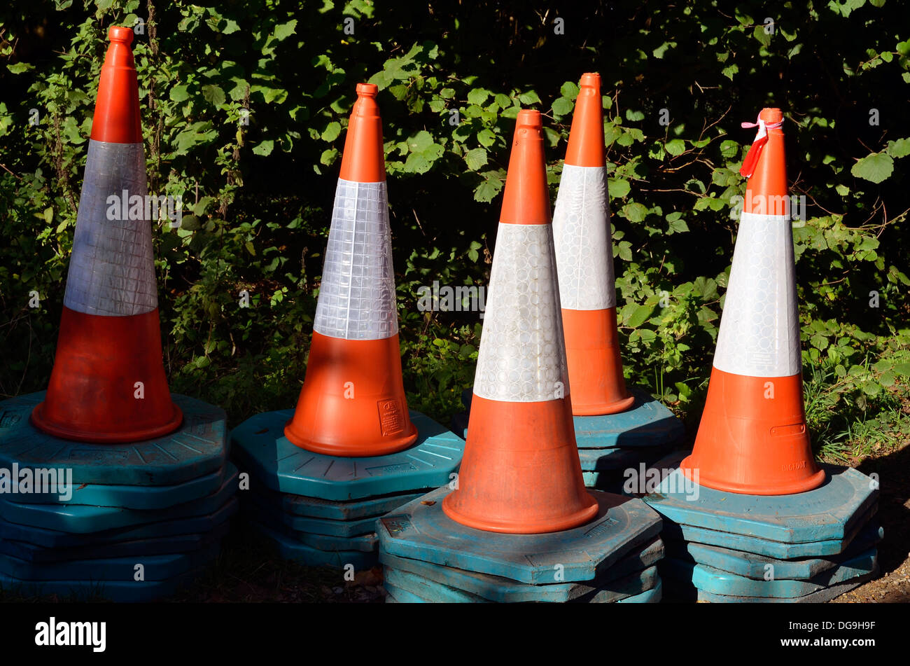 Stack of road cones or traffic cones stored or abandoned in a quiet country lane in Hampshire. - Stock Image