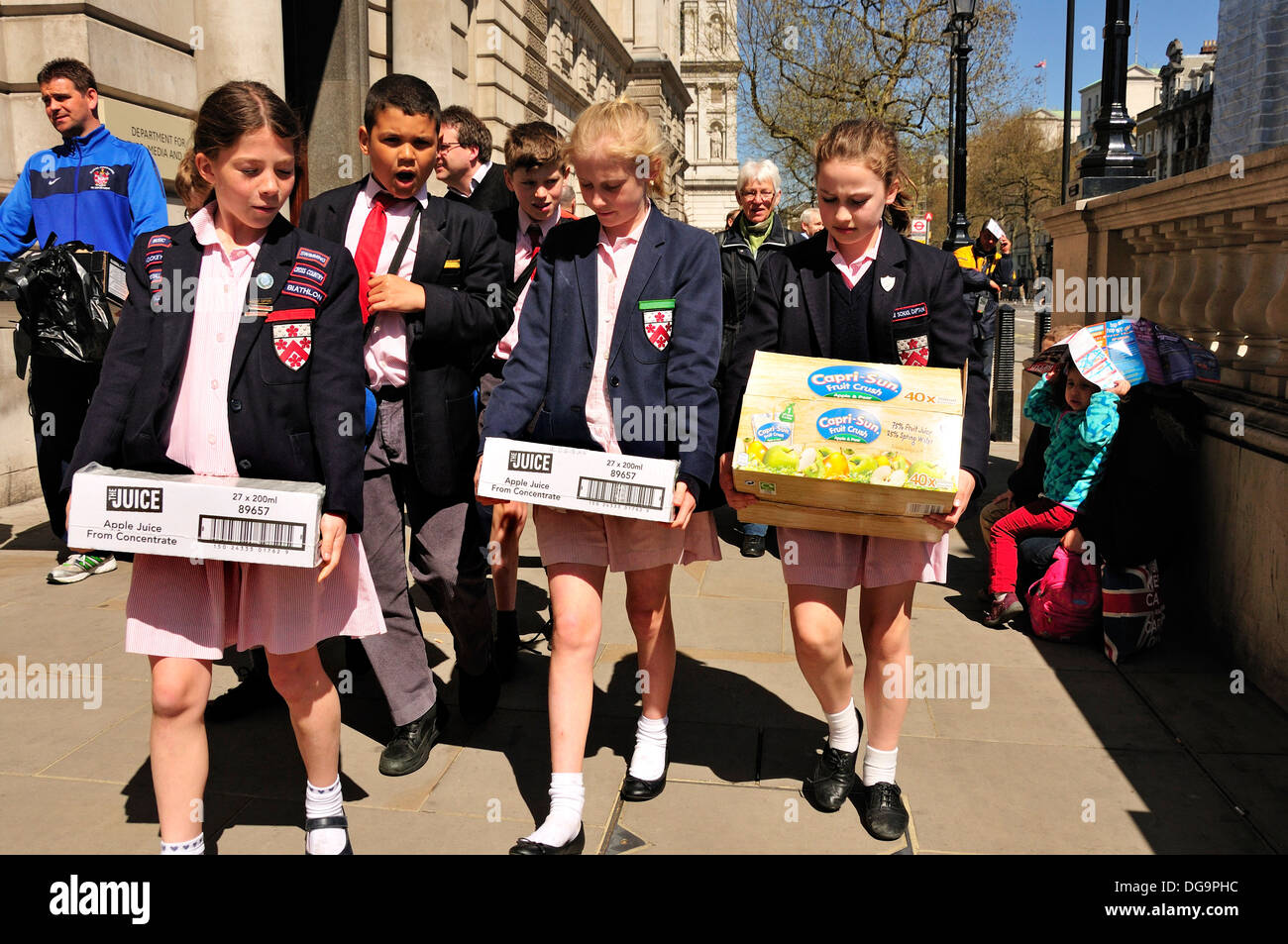London, England, UK. Schoolchildren walking down Whitehall with boxes of fruit juice (no model releases) - Stock Image