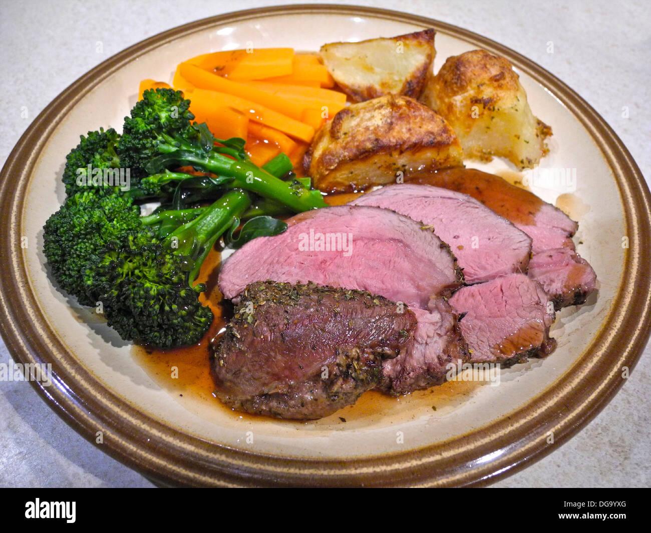 Roast lamb meat with roast potatoes carrots and brocolli rare pink - Stock Image