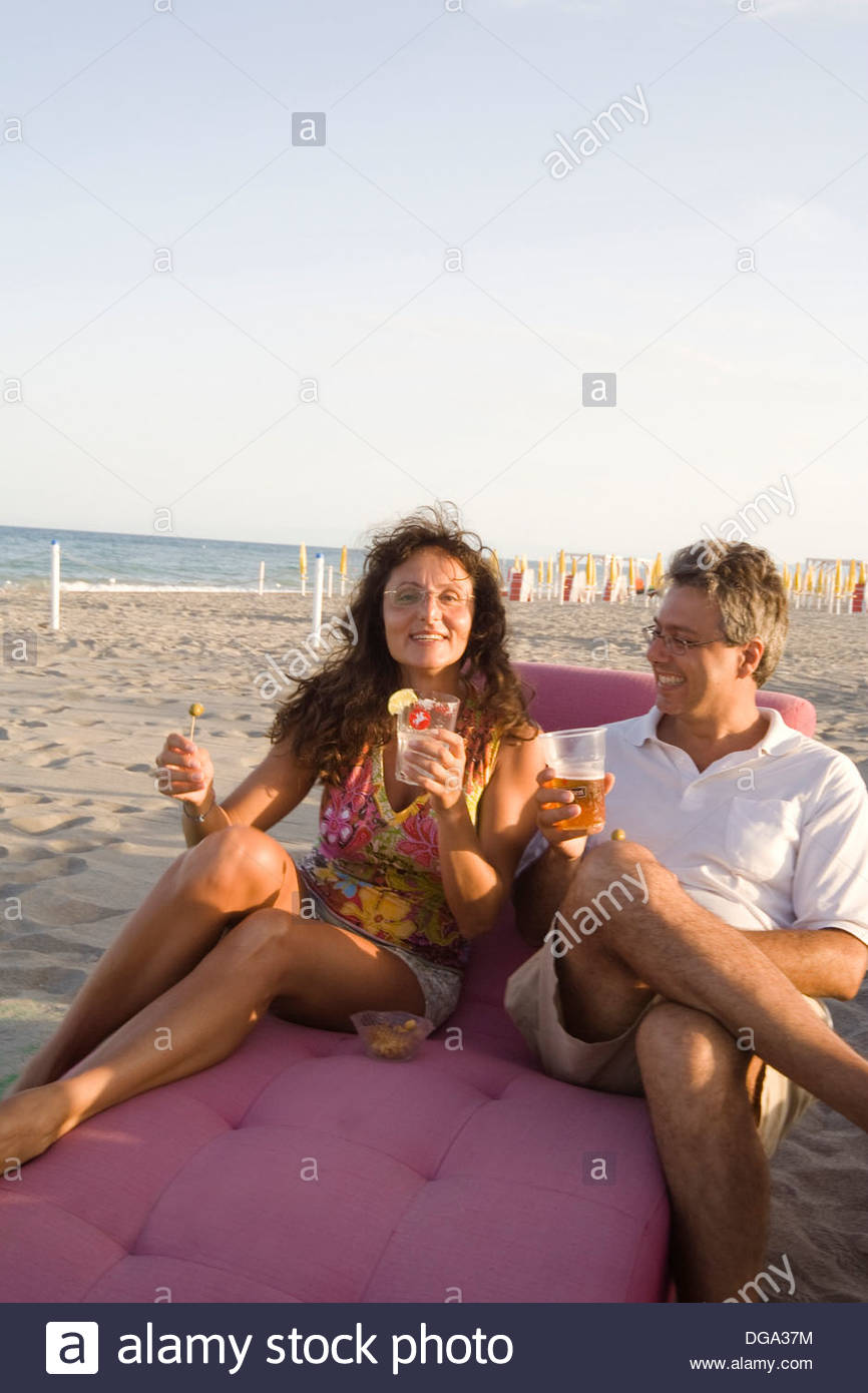 Couple drinking on the beach at sunset - Stock Image