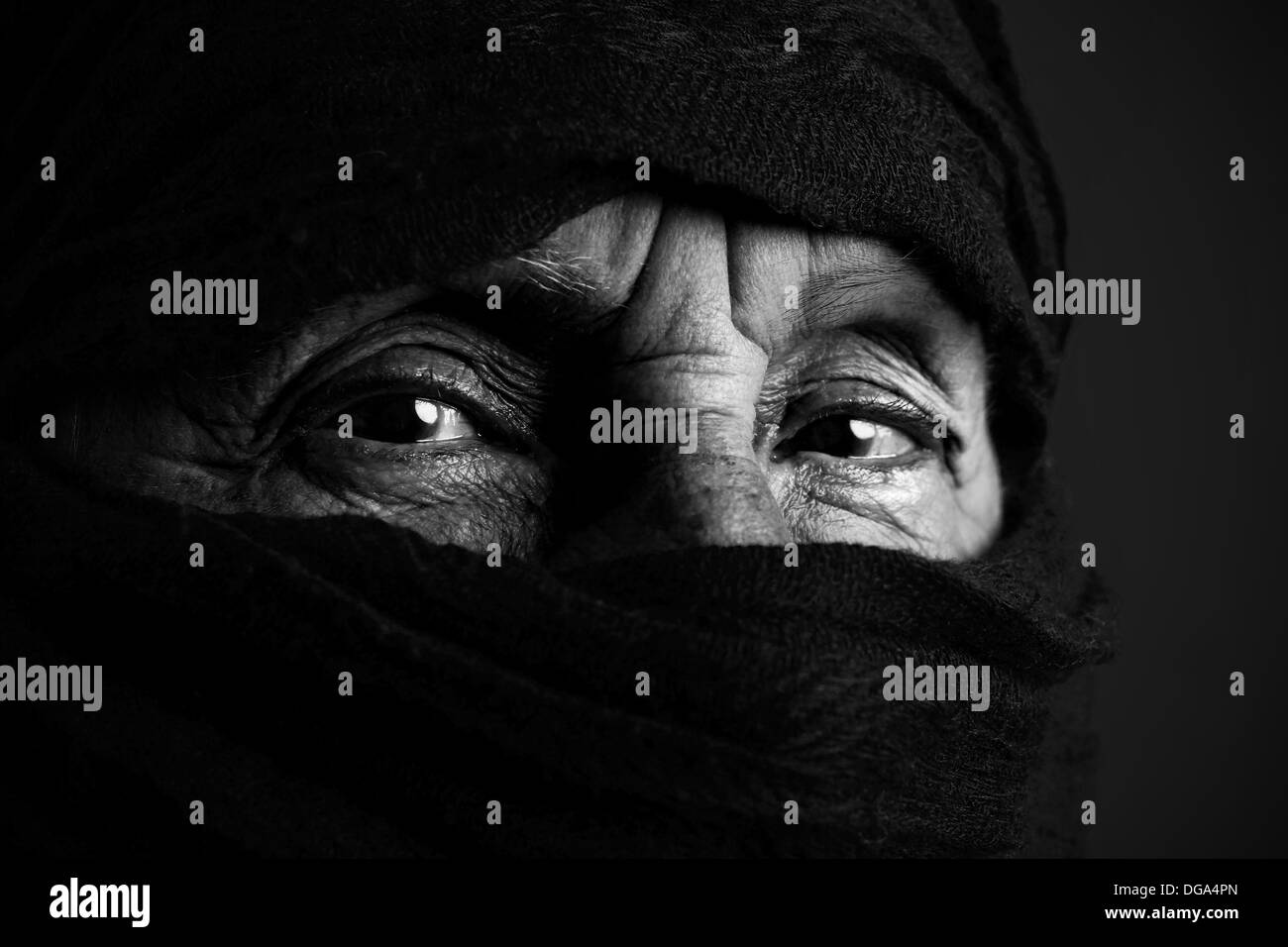 Eyes of senior muslim woman with niqab, looking at camera, black and white - Stock Image