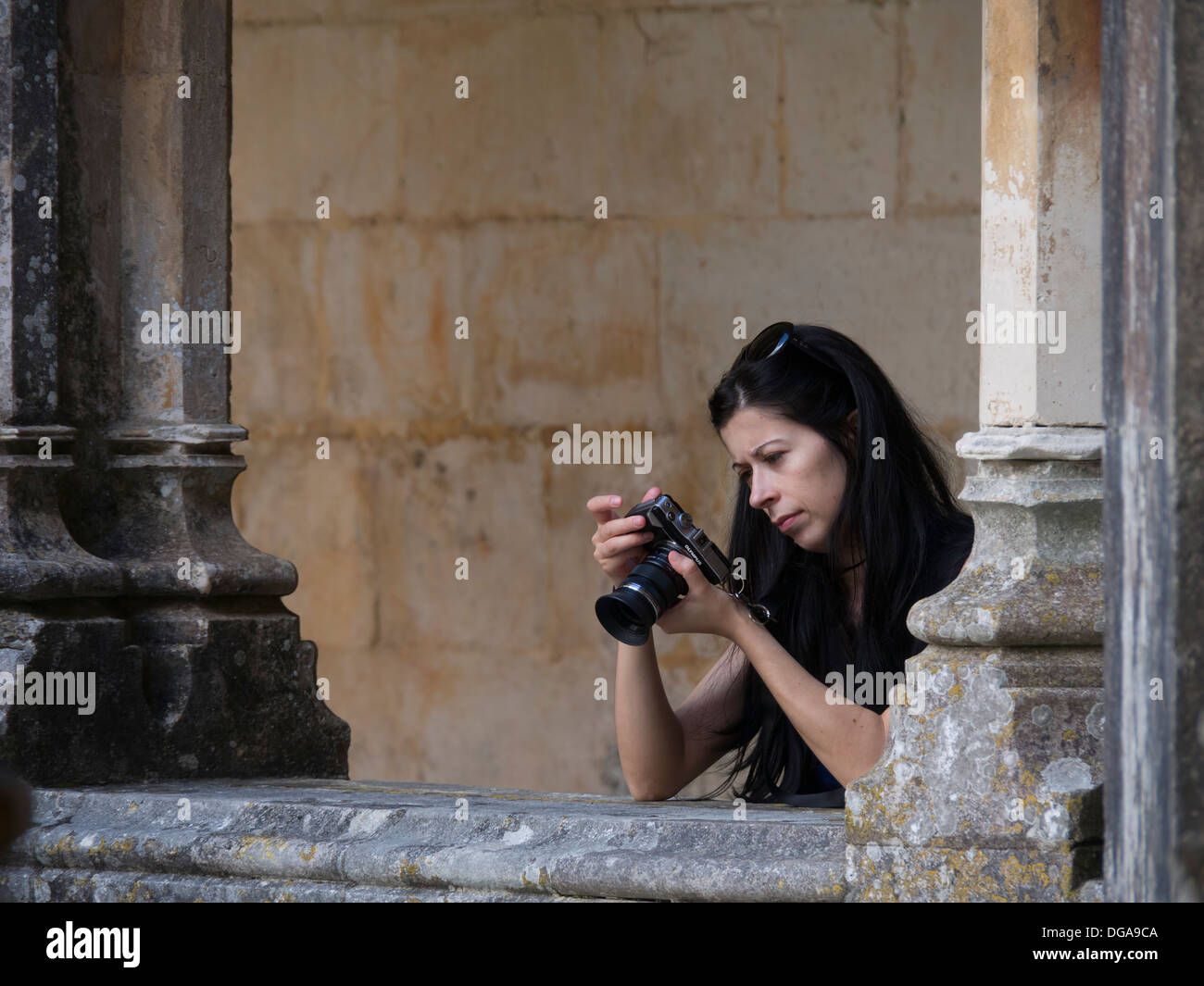 Young woman looking at the LCD on the back of her digital camera while taking pictures - Stock Image