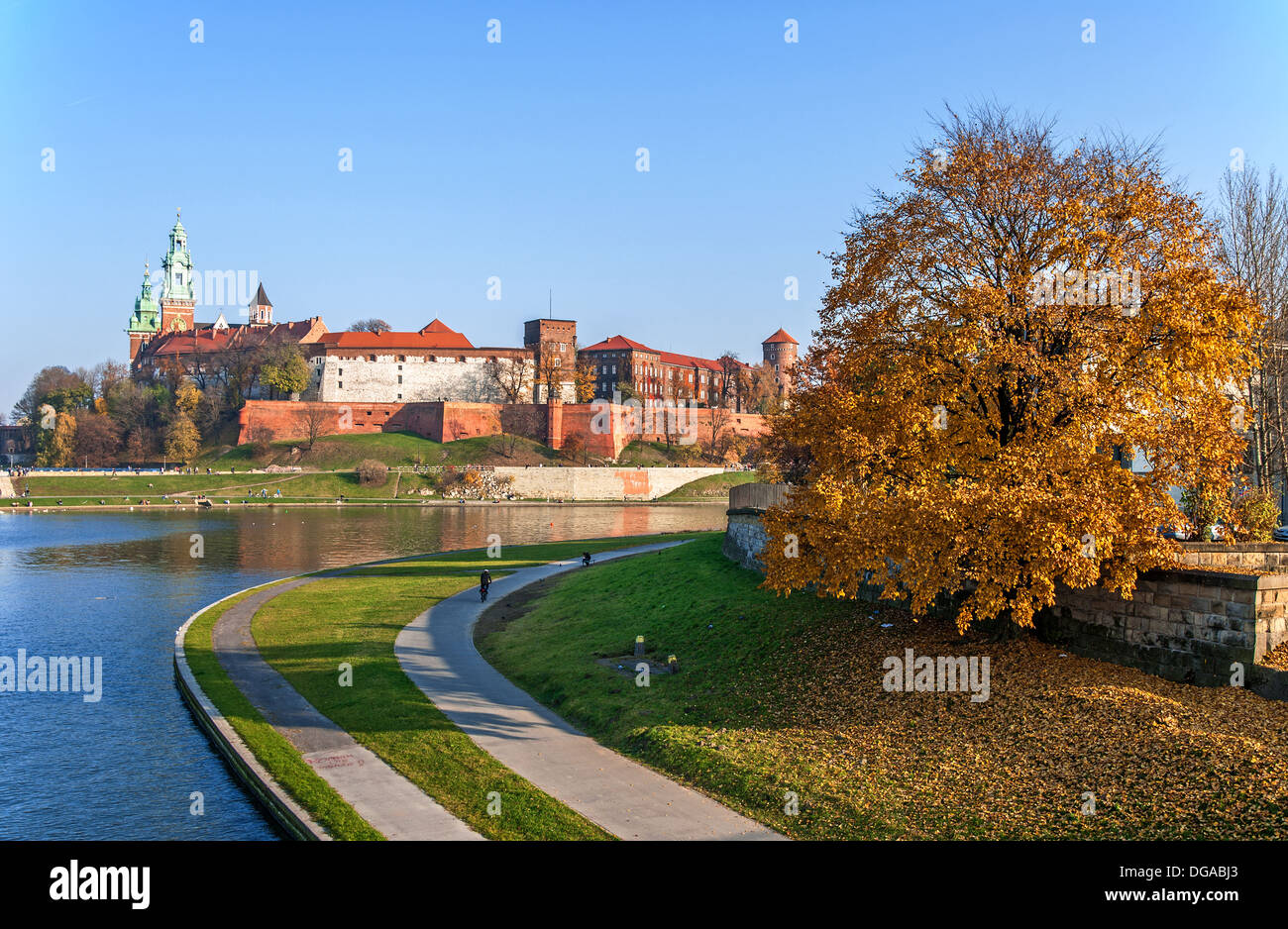 Royal Wawel castle, Vistula river bend, promenades and an autumn tree at sunset in Krakow, Poland - Stock Image