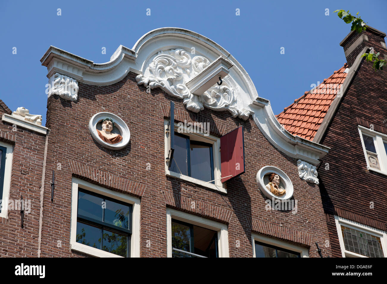Historic facade in Amsterdam with sculptured portraits - Stock Image
