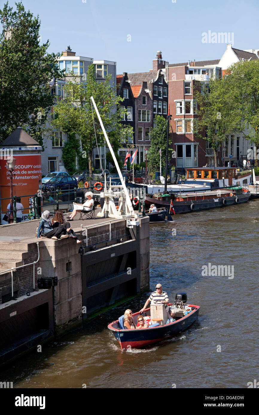 Relaxing besides a lock in the canal in Amsterdam - Stock Image