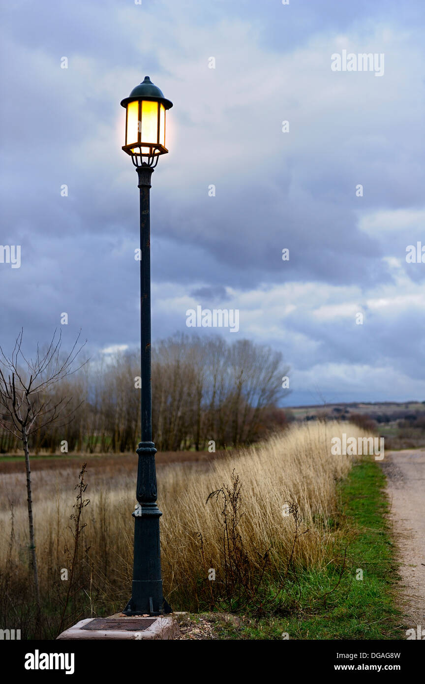 Streetlight illuminating a country road on a stormy sky - Stock Image