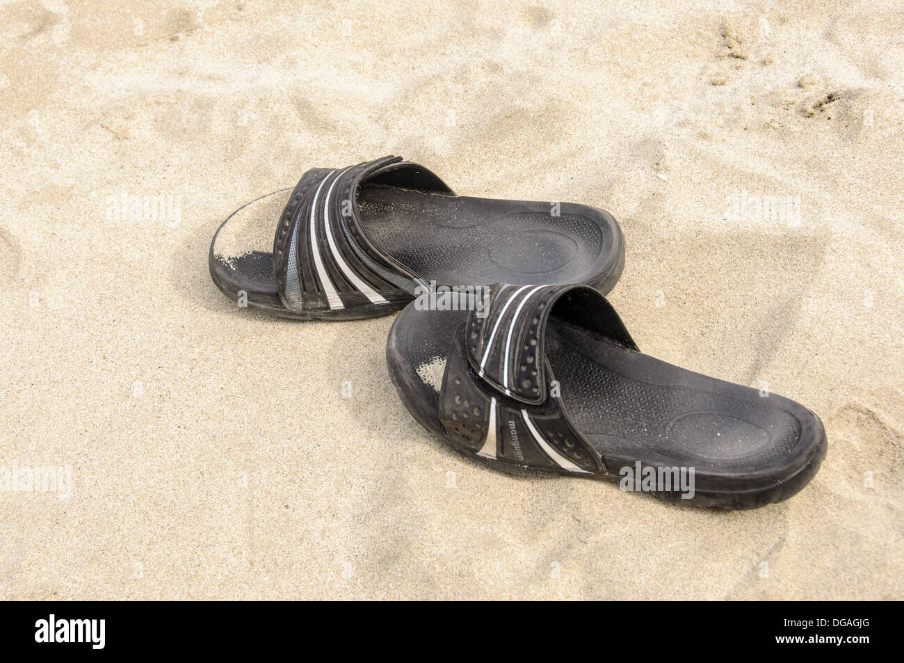Beach slippers, thongs, on a sand beach, symbolizing holidays and vacations Stock Photo