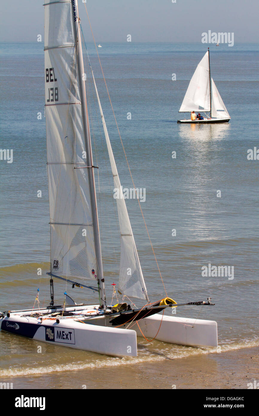 Sailing boat and beached catamaran on beach along the North Sea coast - Stock Image