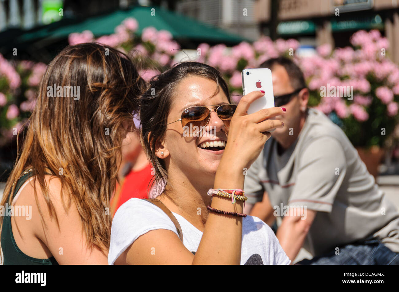 Young Caucasian woman, wearing sunglasses, smiling and taking pictures with an Apple iPhone Stock Photo