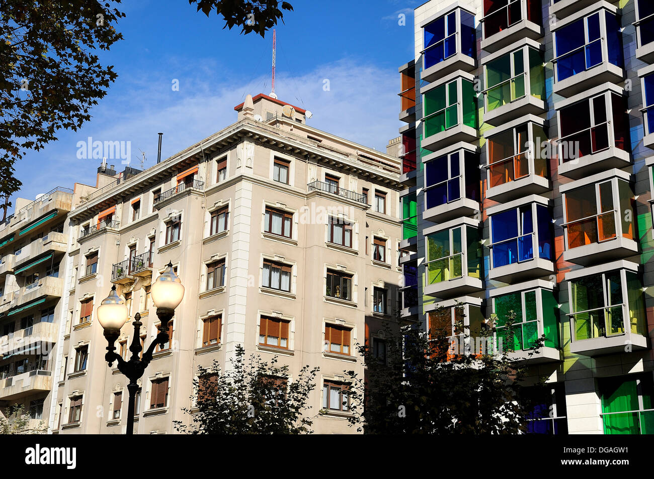 Art Deco façade of the Hotel Hesperia Bilbao crystals with different colored windows as opposed to a classical building Stock Photo