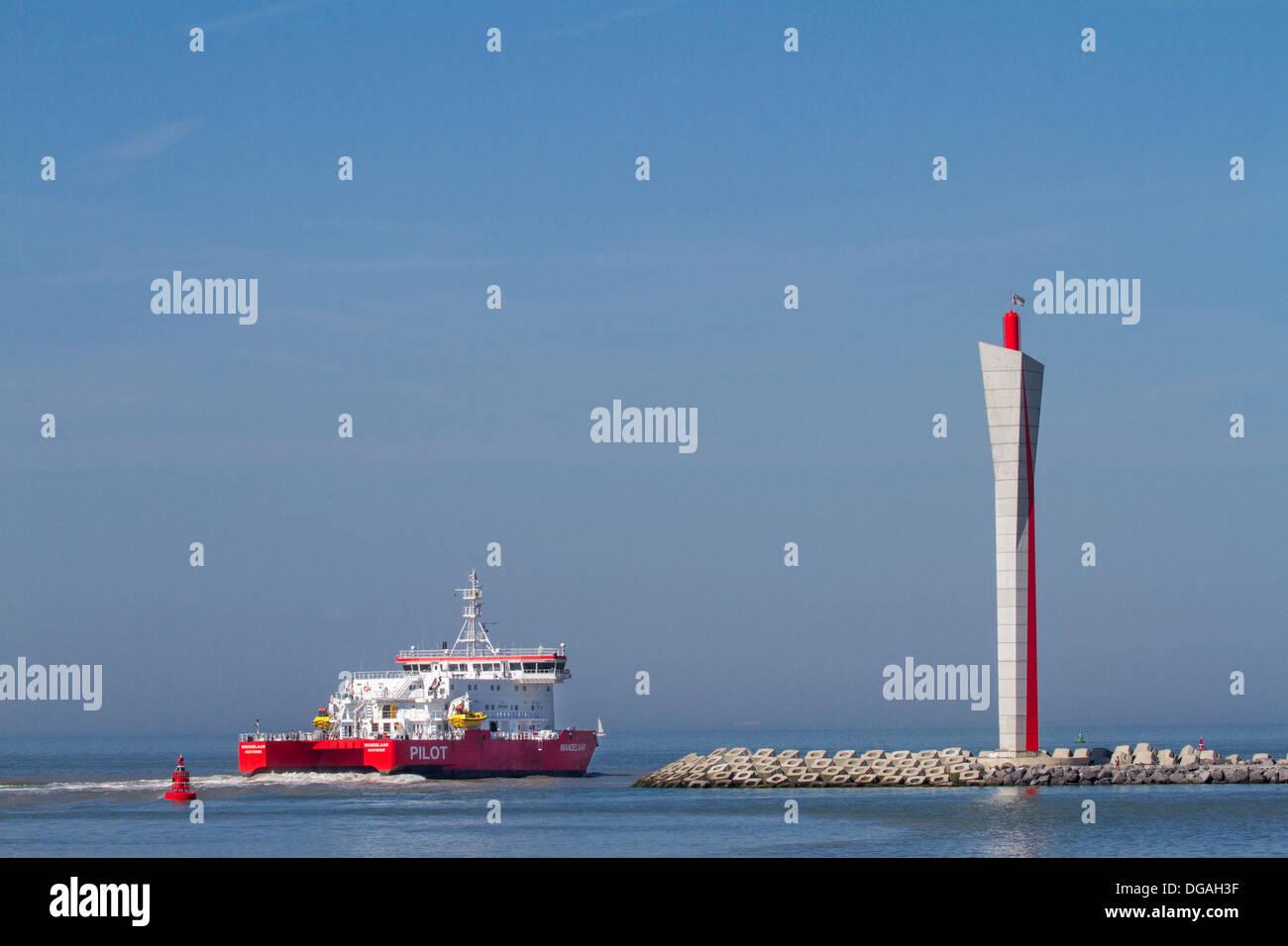 Pilot boat leaving the Ostend harbour past radar tower on the longitudinal embankment along the North Sea coast, Belgium - Stock Image