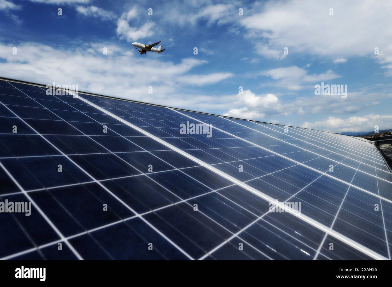 Solar panels on the roof of a modern office building with a plane on final approach to the airport - Stock Image