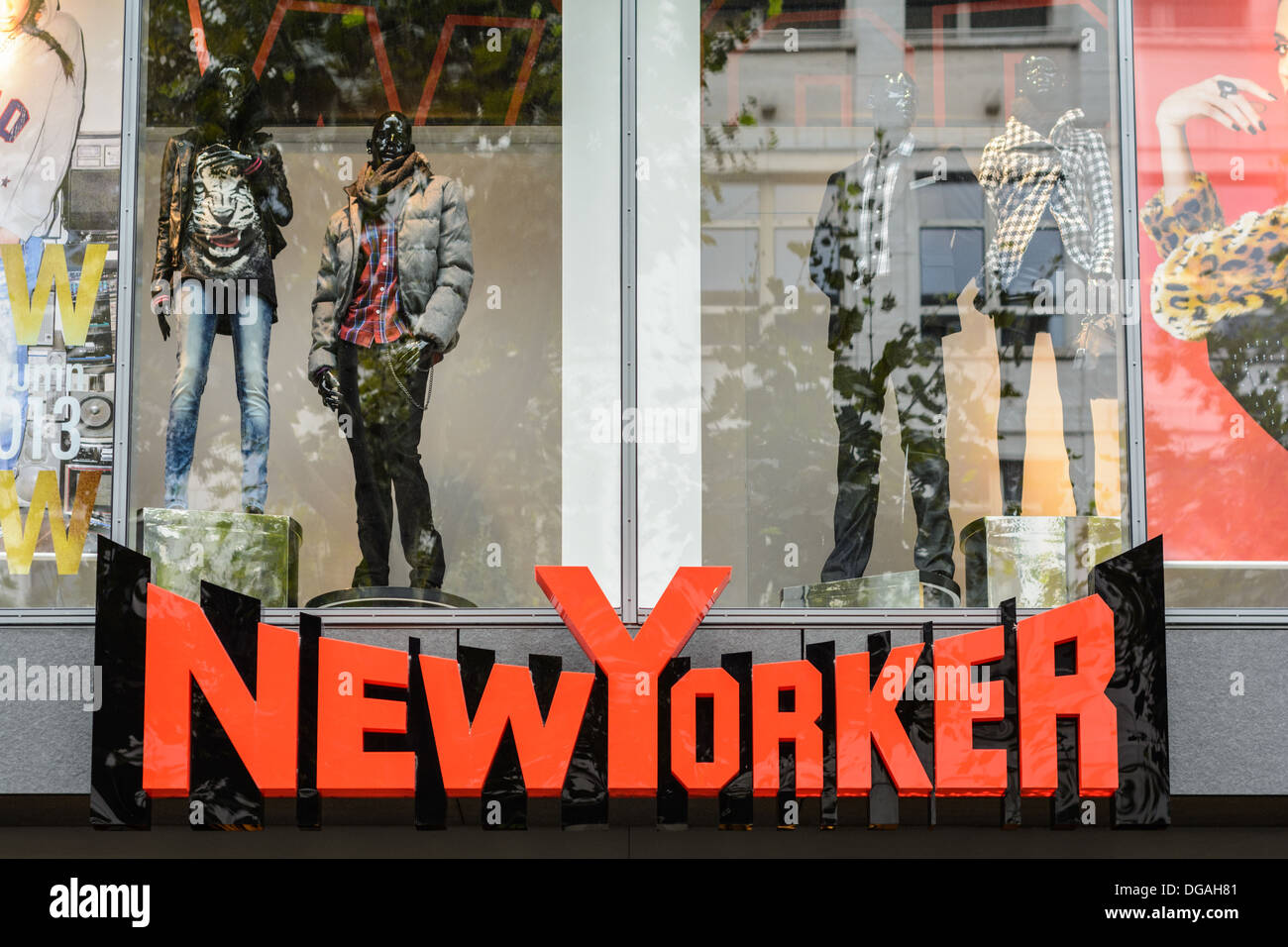 Red illuminated NewYorker company logo sign and shopwindow – international fashion label based in Braunschweig, Stock Photo