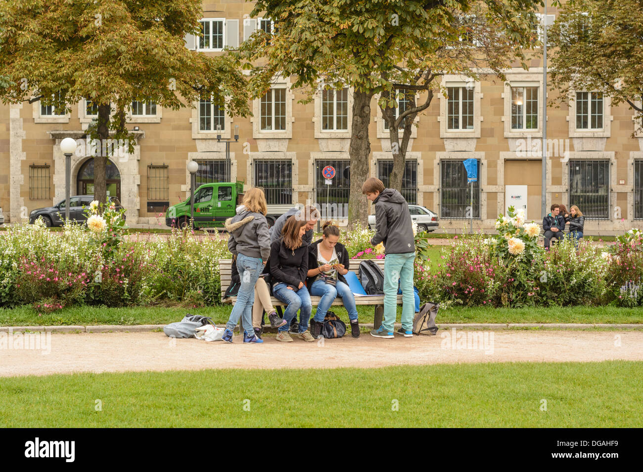 Young Caucasian people, boys and girls, teenagers, chilling out on a park bench - Stuttgart Germany Stock Photo