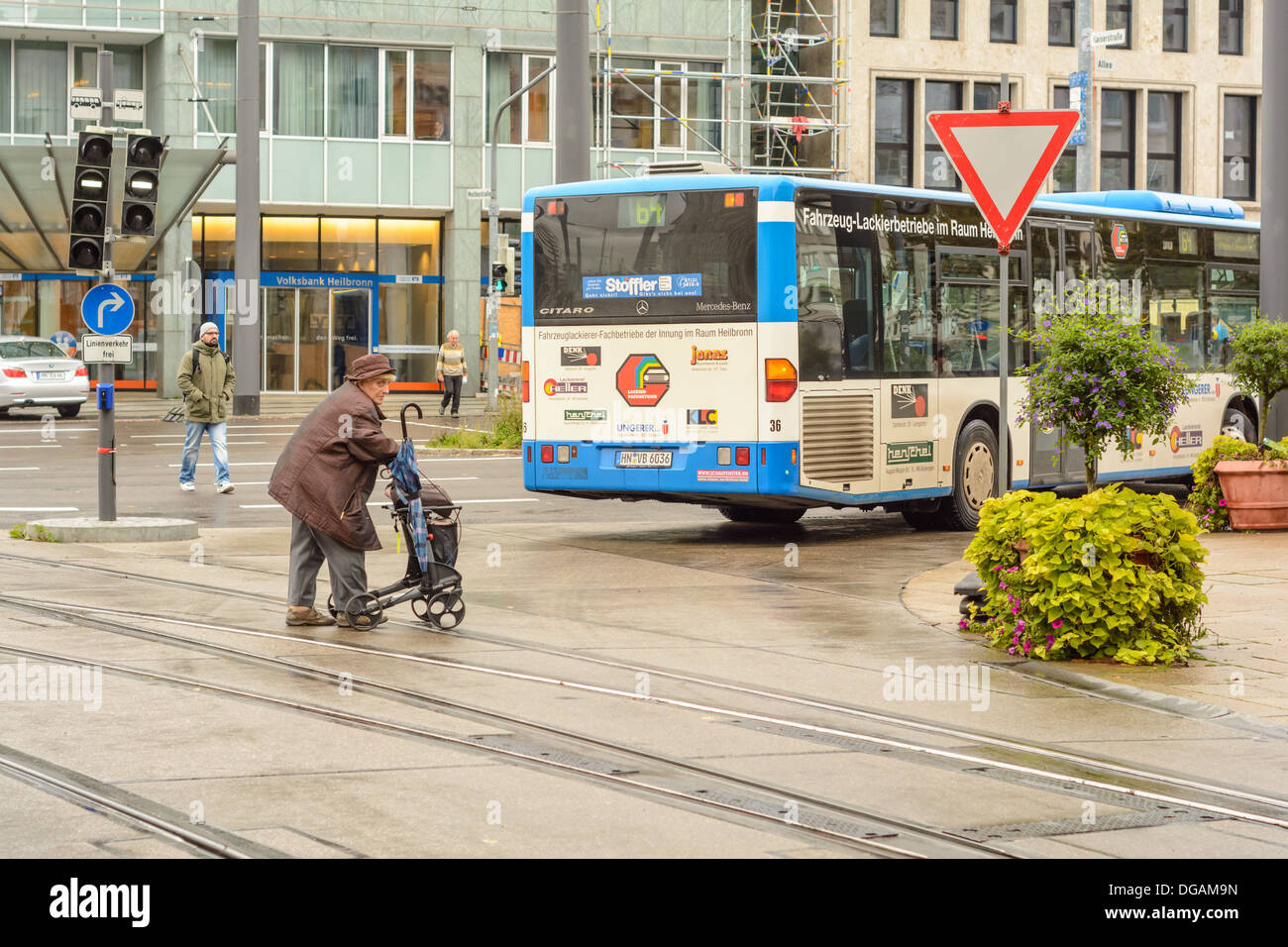 Old woman with wheeled walker and other people cross over a road with tram rails, behind a public bus in the city Heilbronn, Germany - Stock Image