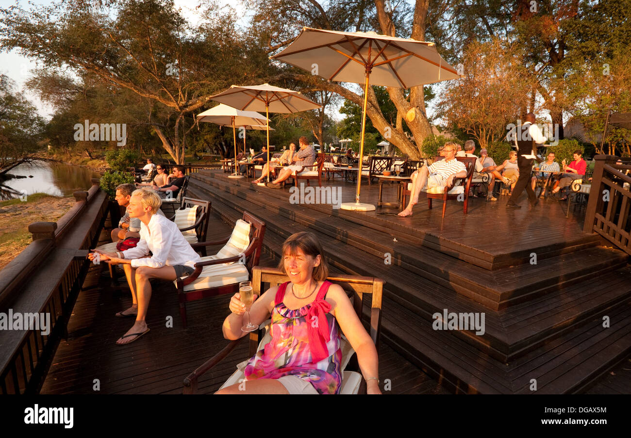 Hotel guests watching the sunset from the Sunset Veranda bar, Royal Livingstone Hotel, Victoria Falls, Zambia Africa - Stock Image