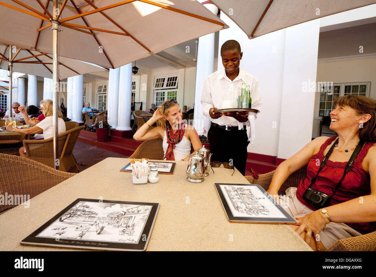 Guests ordering drinks on the terrace, the Victoria Falls Hotel, Zimbabwe Africa - Stock Image