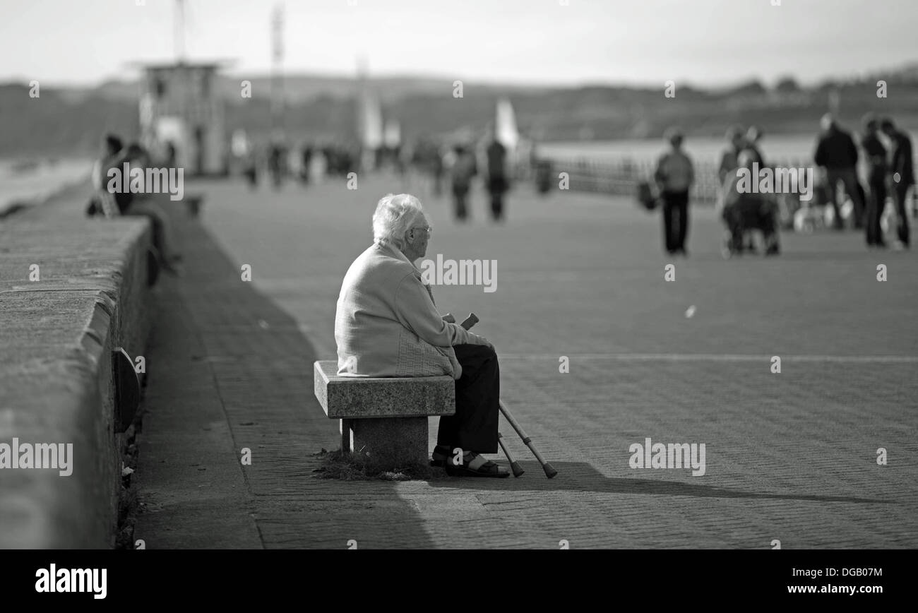 old lady alone Mountbatten Pier Plymouth sitting with walking sticks in Black and white - Stock Image