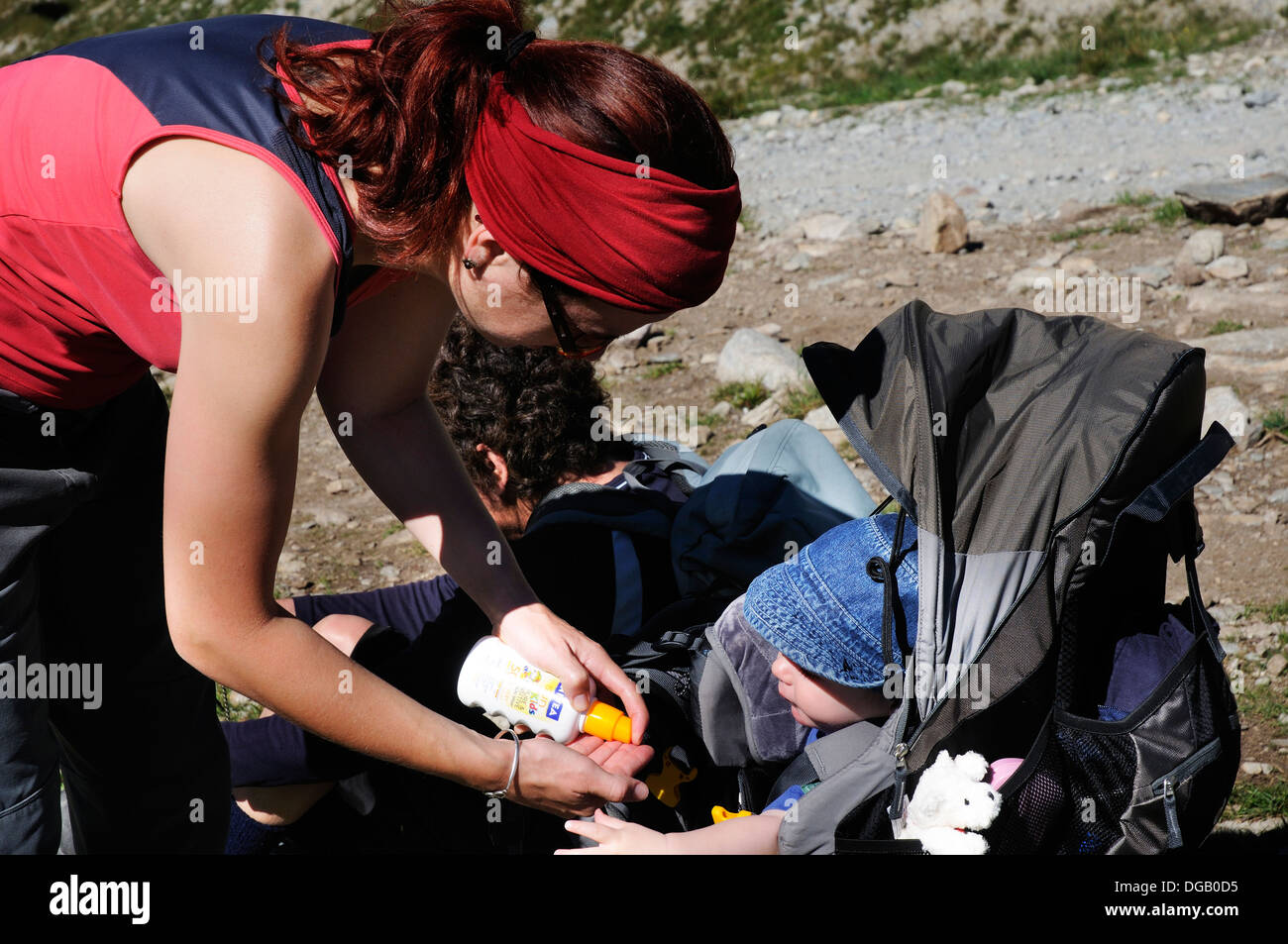 A mother putting suncream on a baby - Stock Image