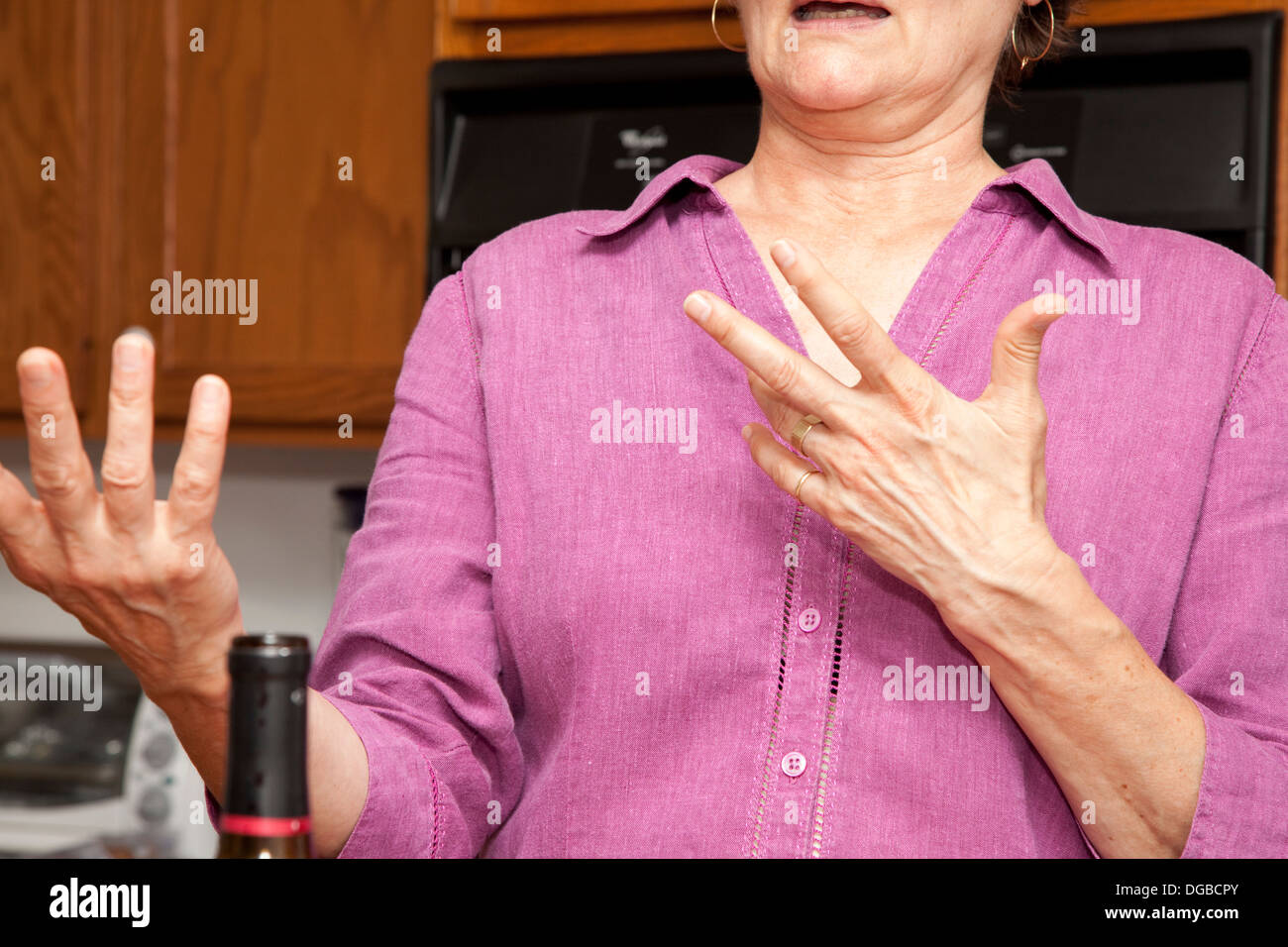 Woman expressing herself with her hands in the kitchen. St Paul Minnesota MN USA - Stock Image