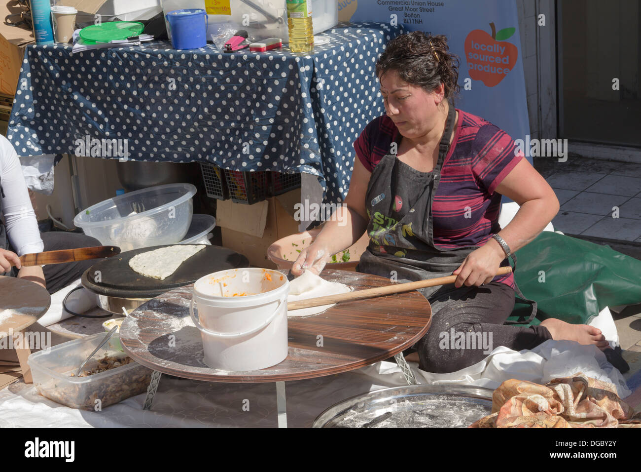 Members of the Lakamka project make Turkish bread at 'The Kitchen on Great Moor Street' stall at the Bolton Food Festival 2013. - Stock Image
