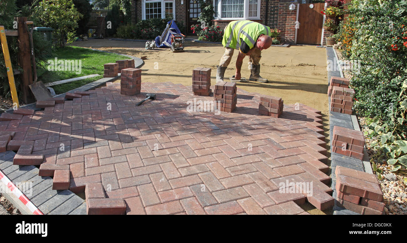 Stage 4 of a project to lay a block paved drive.Lying the blocks on sand. - Stock Image