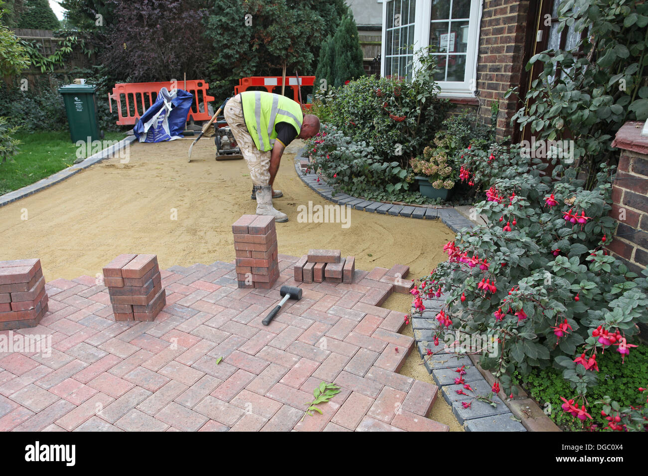 Stage 5 of a project to lay a block paved drive.Lying the blocks on sand. - Stock Image