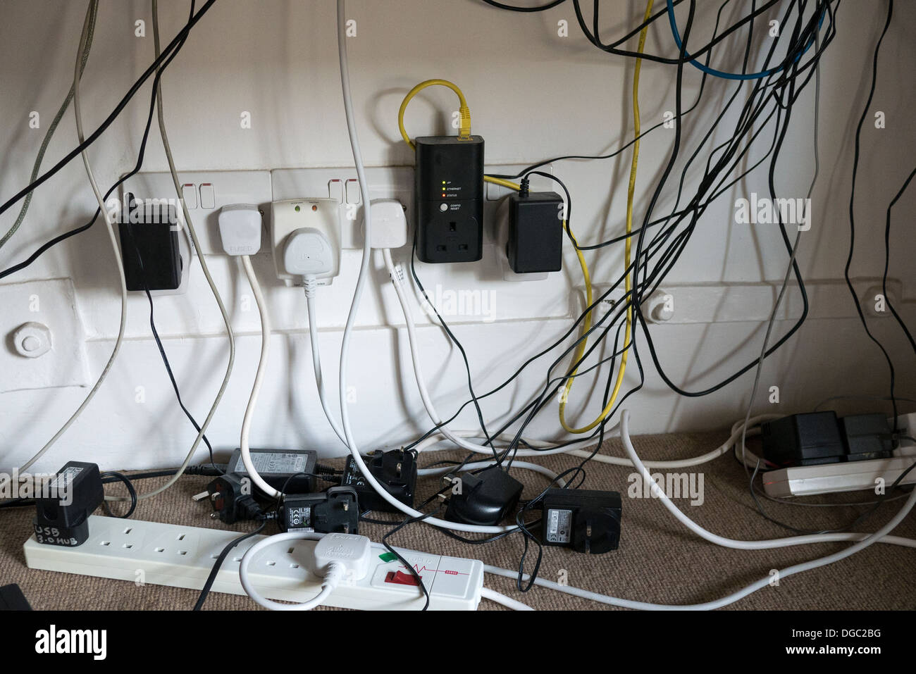 a jumble of power cables and computer wires under a desk