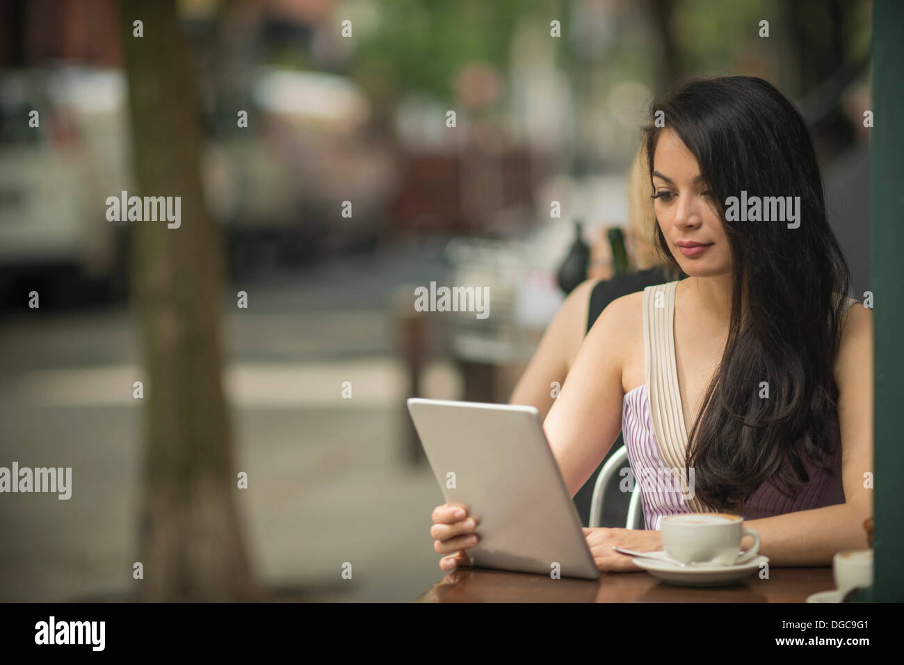 Mid adult women using digital tablet in pavement cafe - Stock Image