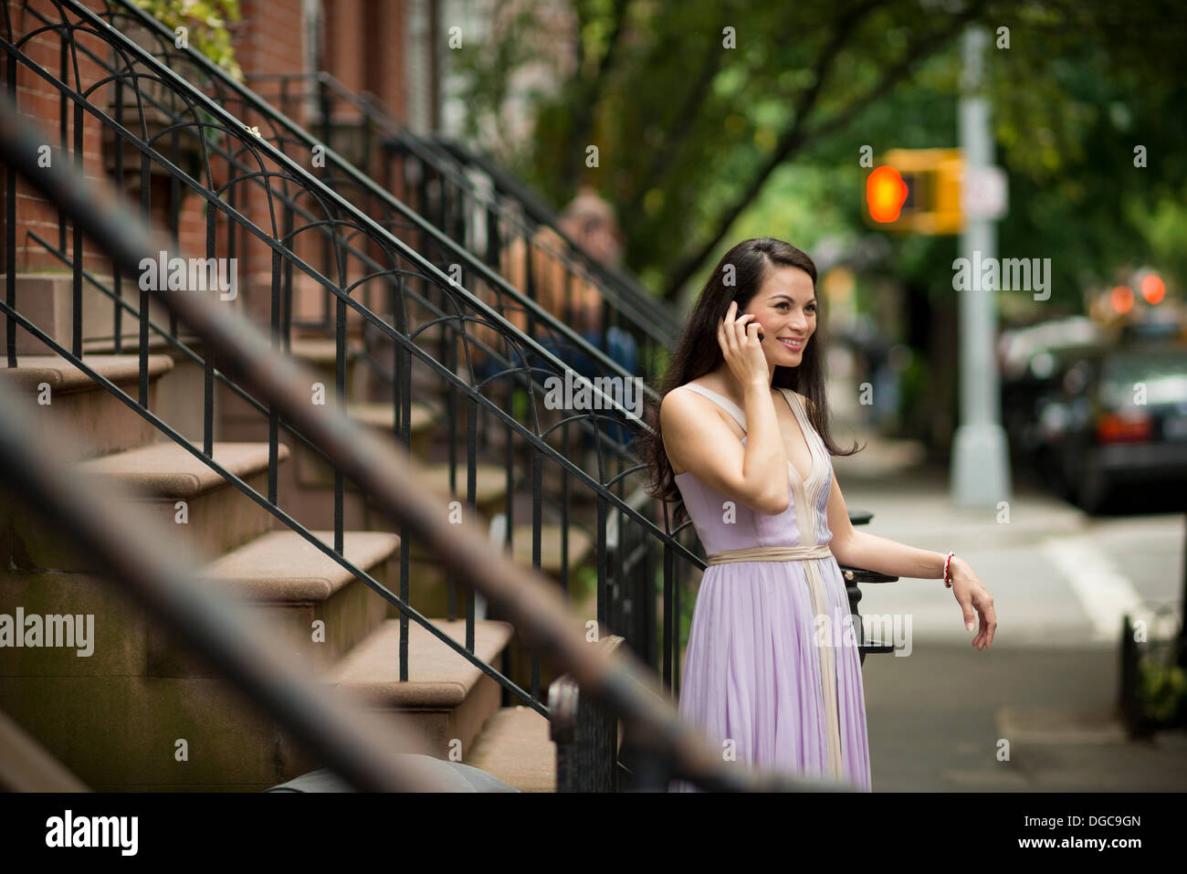 Mid adult women using mobile phone by brownstone buildings in Greenwich, New York - Stock Image