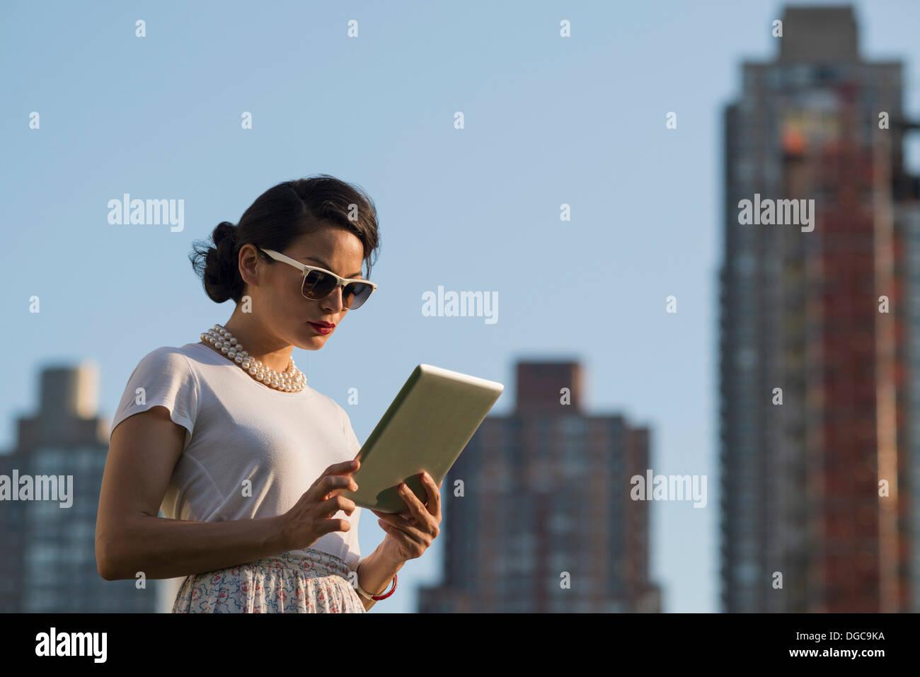 Mid adult women using digital tablet, Manhattan, New York - Stock Image