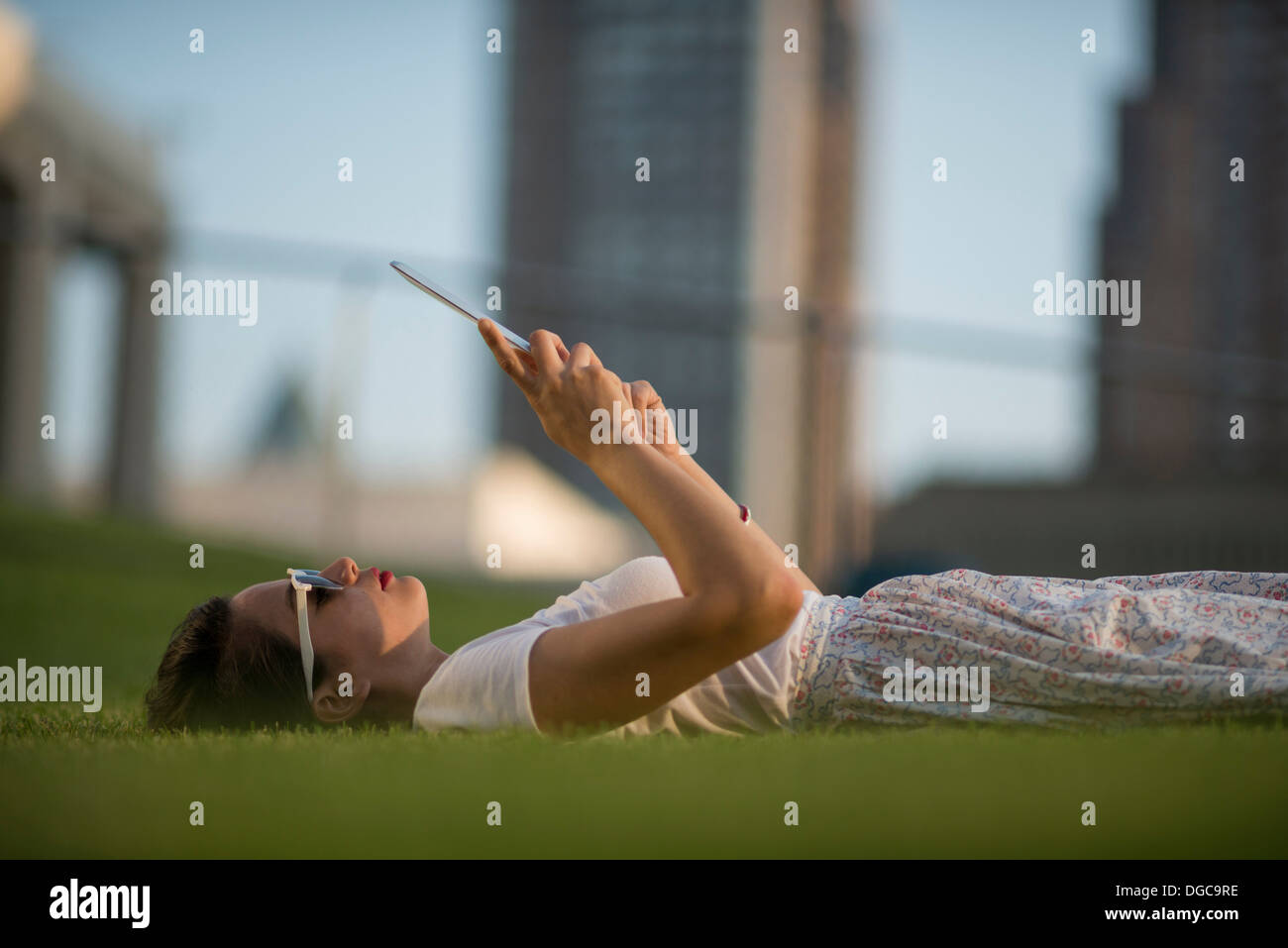 Mid adult women lying in park using digital tablet - Stock Image