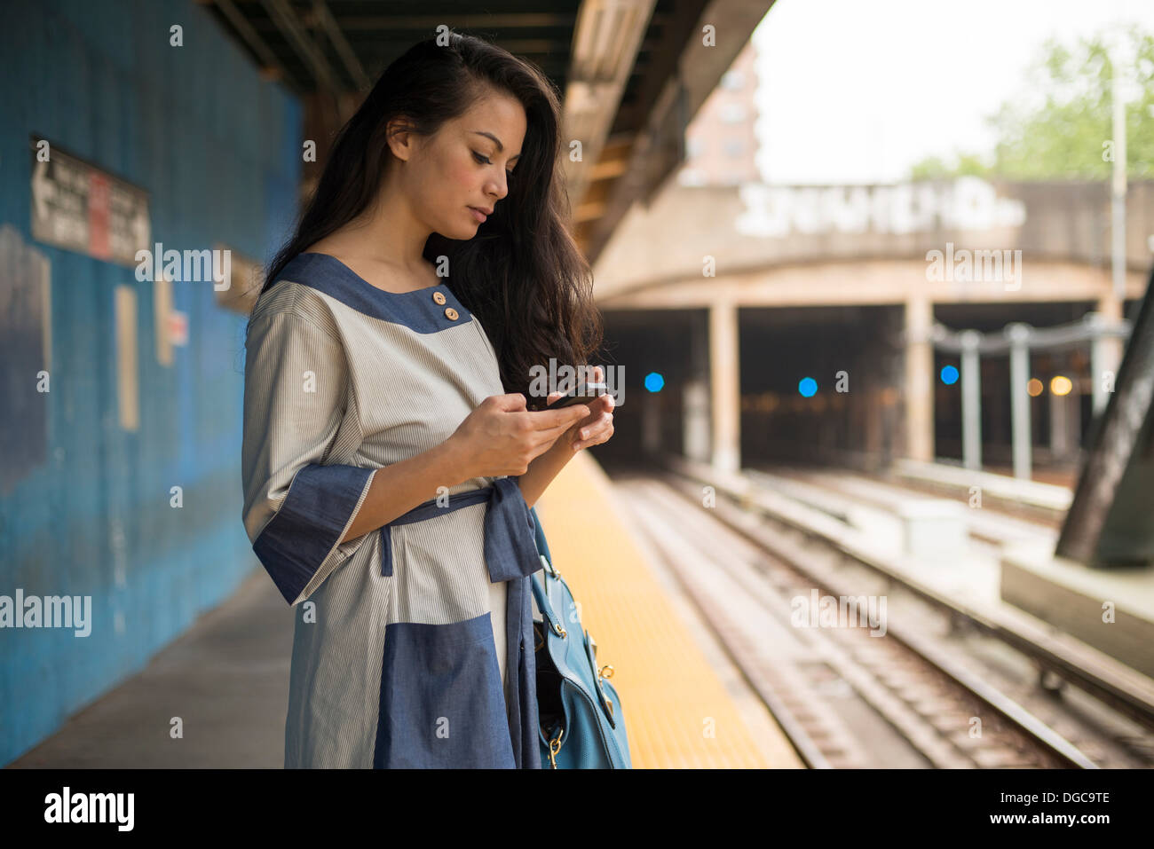 Mid adult women using mobile phone on subway platform, Brooklyn, New York - Stock Image