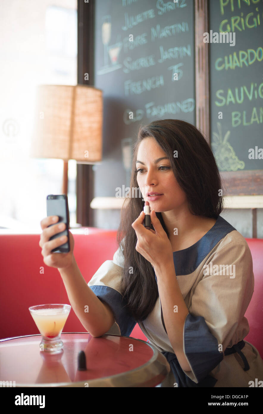 Mid adult women using mobile phone to apply lipstick in restaurant - Stock Image