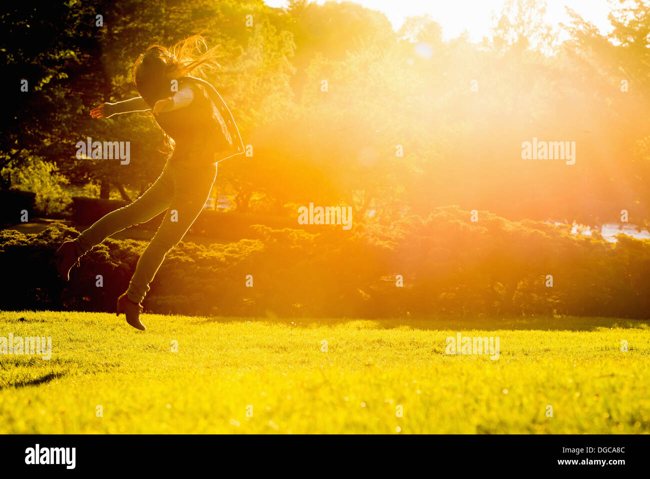 Young female jumping mid air in park - Stock Image