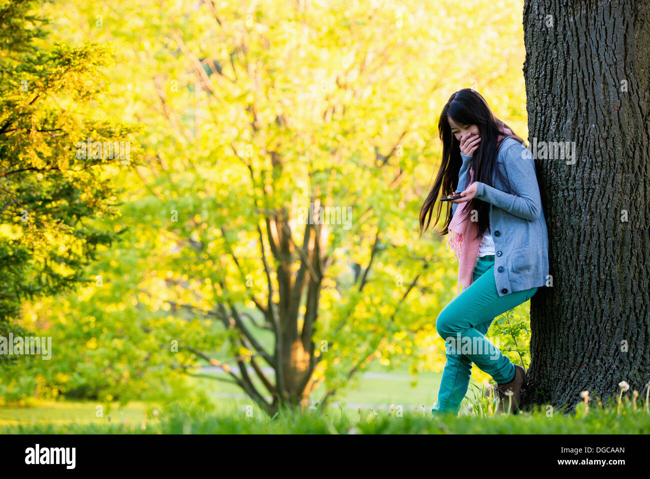 Young female laughing at mobile phone in park - Stock Image