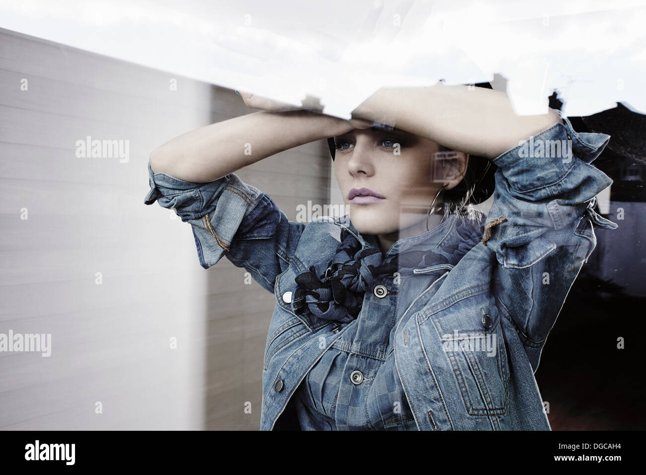 Young woman looking out of window - Stock Image