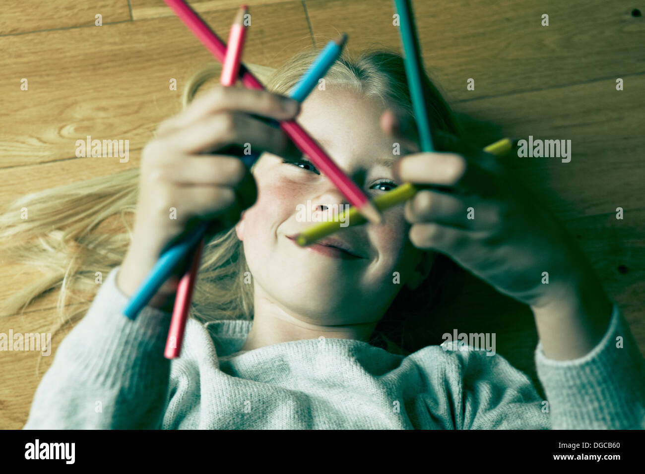 Young girl lying on floor looking at coloured pencils - Stock Image