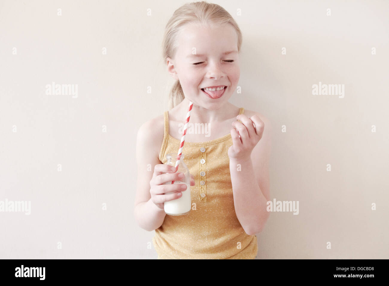 Young girl sticking tongue out and holding glass of milk - Stock Image