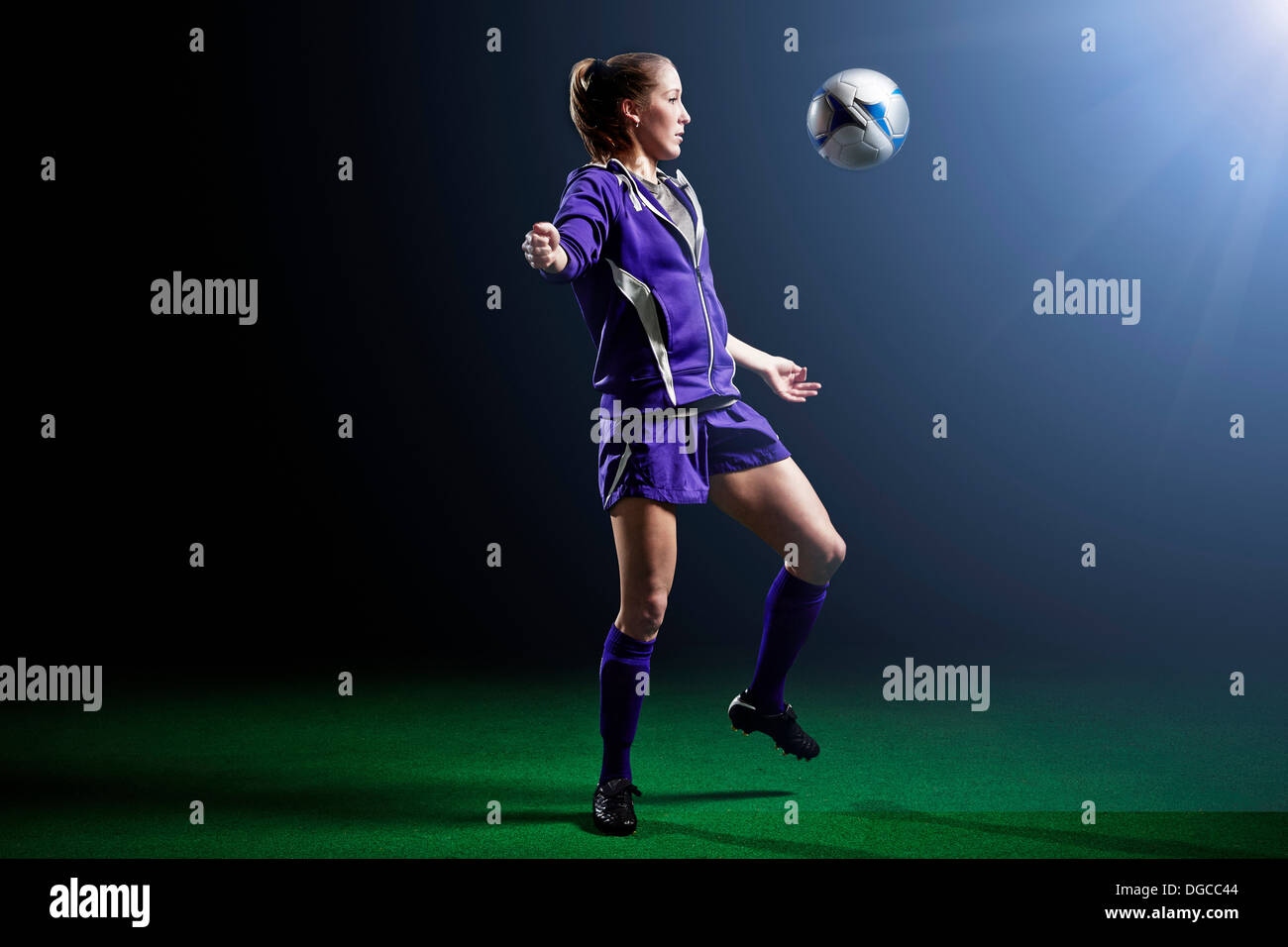 Young female soccer player with ball - Stock Image