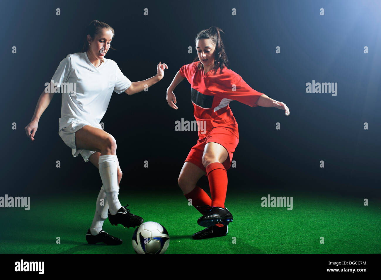 Two female soccer players tackling ball - Stock Image