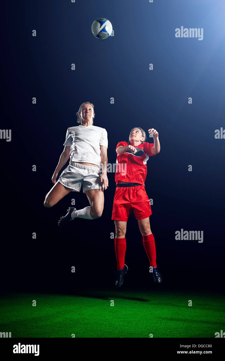 Two female soccer players heading ball - Stock Image