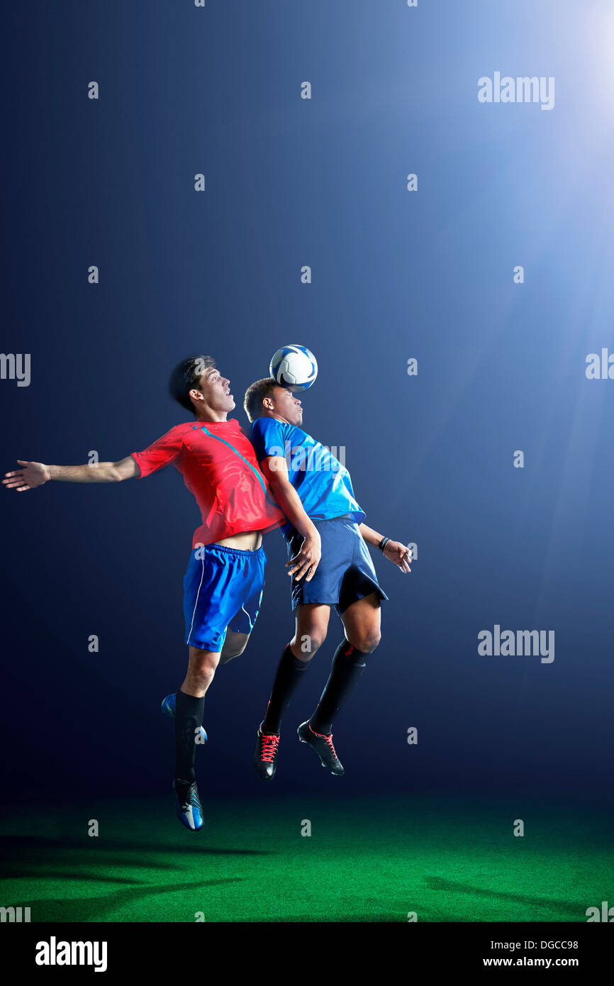 Male soccer players heading ball - Stock Image