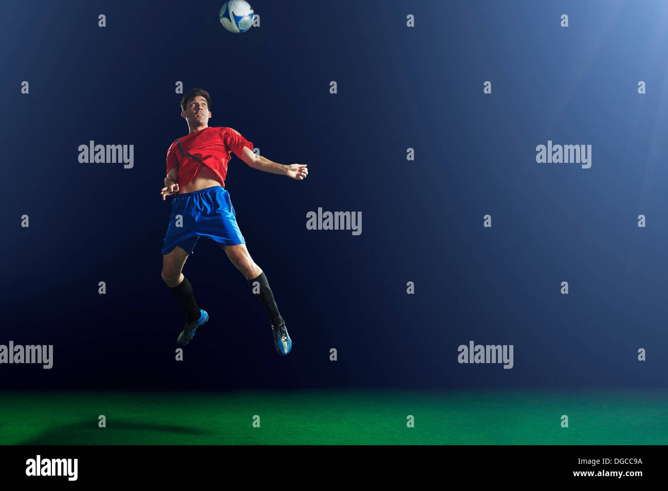 Young male soccer player heading ball - Stock Image