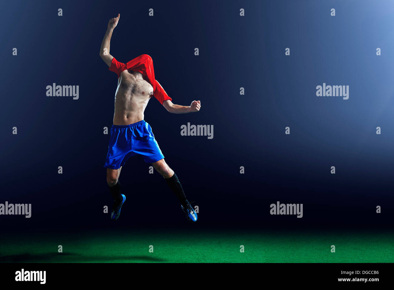 Male soccer player celebrating with shirt over head - Stock Image