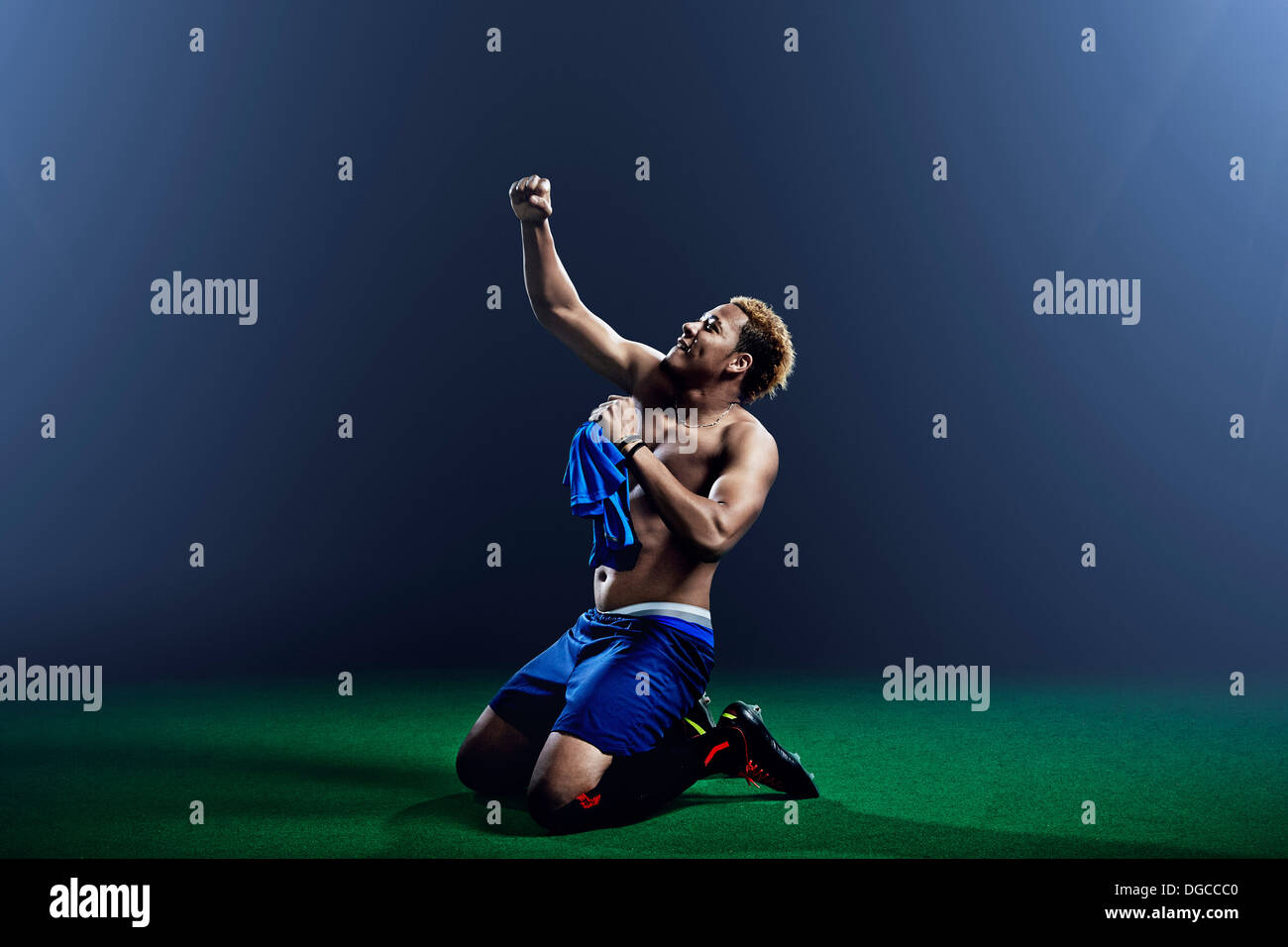 Male soccer player kneeling with arm raised - Stock Image