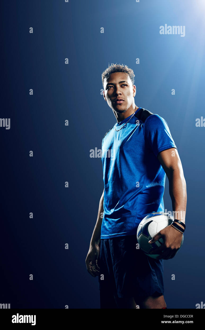 Portrait of male soccer player with football - Stock Image