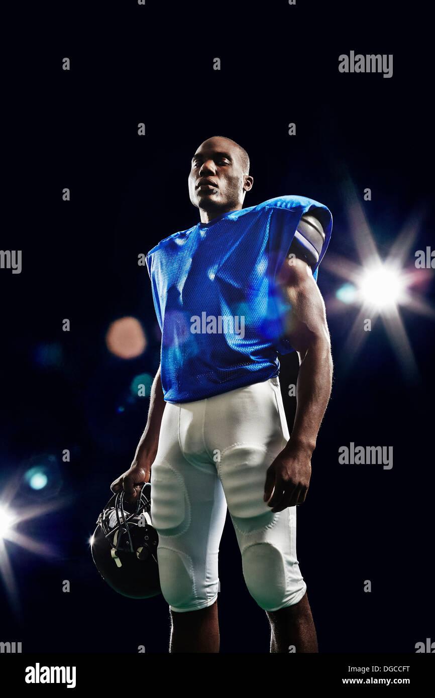 Portrait of american football player holding helmet - Stock Image